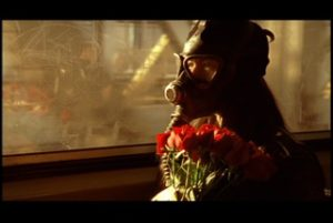 Person wearing a gasmask and holding roses commuting on the train. Still image from Shanti Thakur's film Skypeople