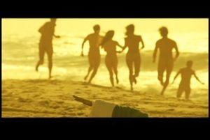 "People running to the ocean shore. Still image from Shanti Thakur's film ""Sky People"""