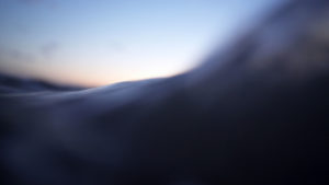 A wave sloshes over most of the image, filling the bottom half of the frame with dark blue water, while the top half shows a mostly cloudless sky with a gradient that starts at the horizon and dissolves from pink to white to light blue.
